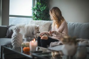 woman on couch with white fluffy dog  and coffee table with candles