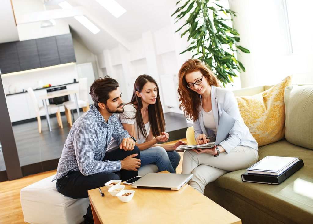 Agent meeting indoors on a couch with man and woman and pointing at a contract