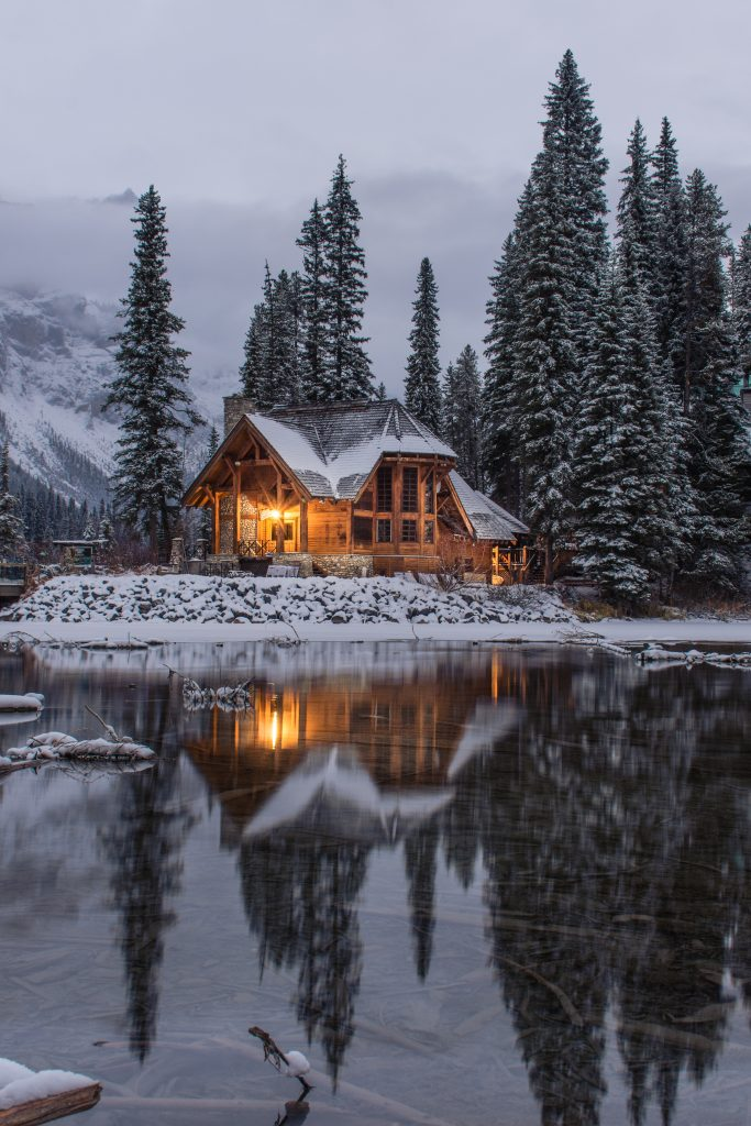 winter home on lake with snow on roof at twilight