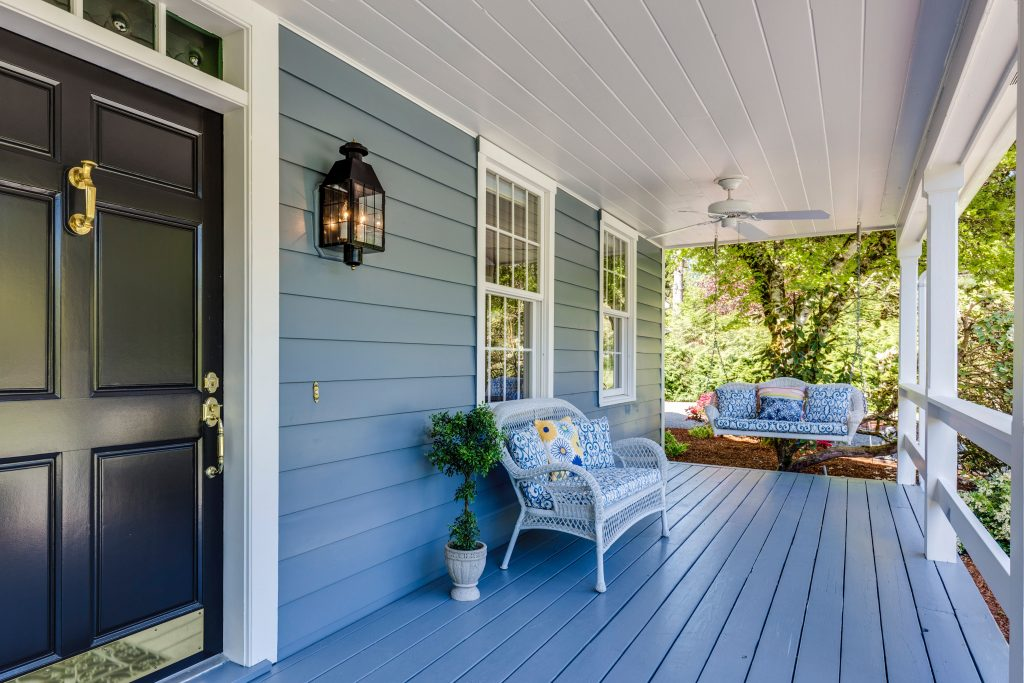 front porch of home painted blue with navy front door, bench, and swinging chair.