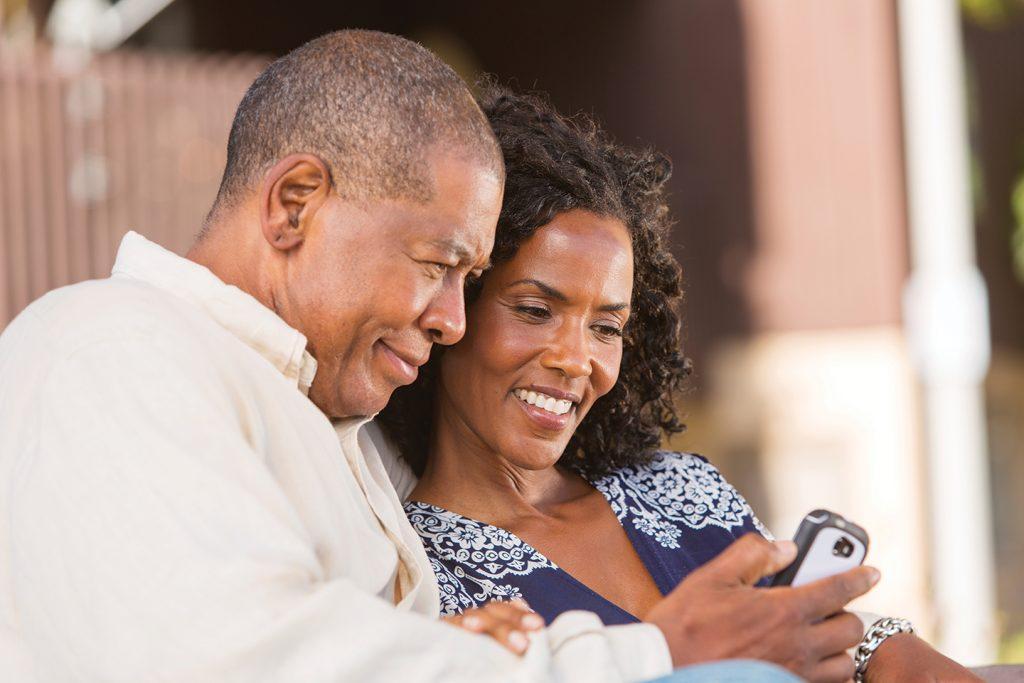 man and woman look at phone screen