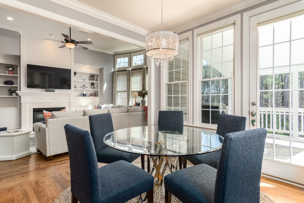Family and dining room with blue chairs and patio in view
