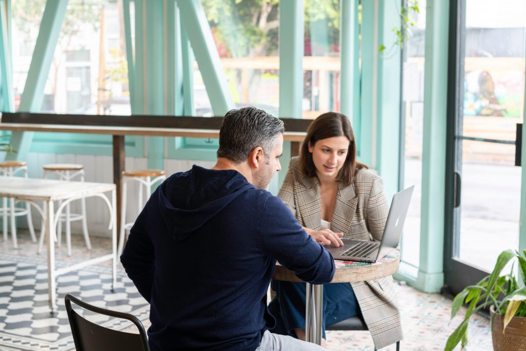Man and woman in cafe looking at computer screen together.