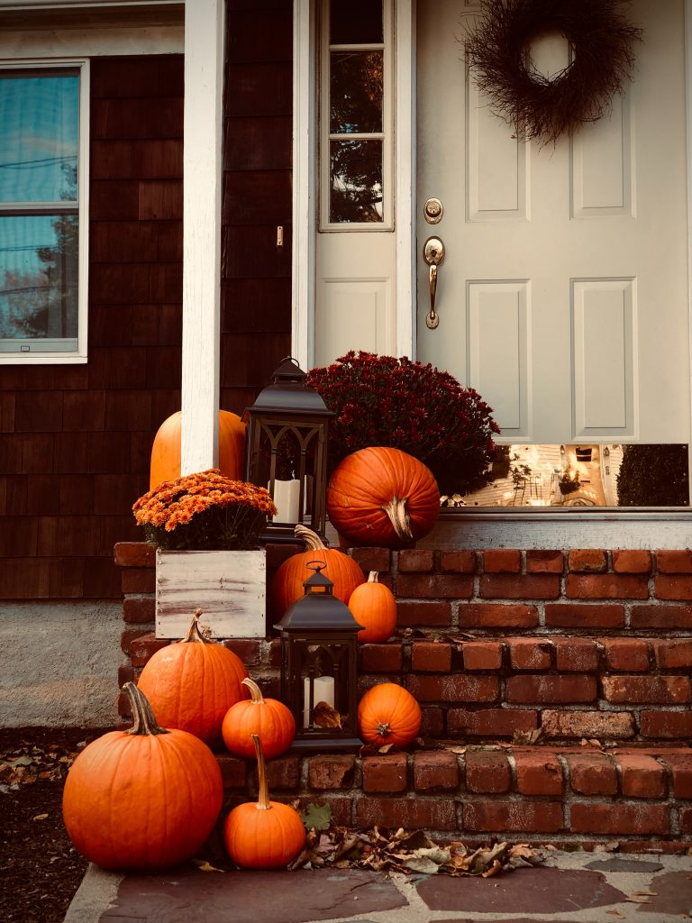 brick front step of home with white door. Orange and red fall leaves, pumpkins, mums, and a lantern.