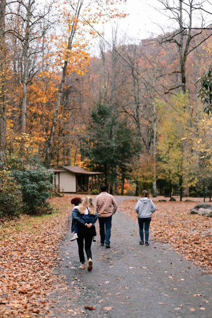 family of 4 walking down tree lined path with leaves on the ground.